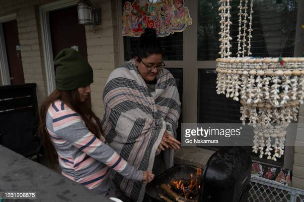 Karla Perez and Esperanza Gonzalez warm up by a barbecue grill during power outage caused by the winter storm on February 16, 2021 in Houston, Texas....
