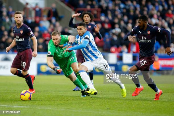Karlan Grant of Huddersfield Town bursts between Bernd Leno and Ainsley MaitlandNiles of Arsenal during the Premier League match between Huddersfield...