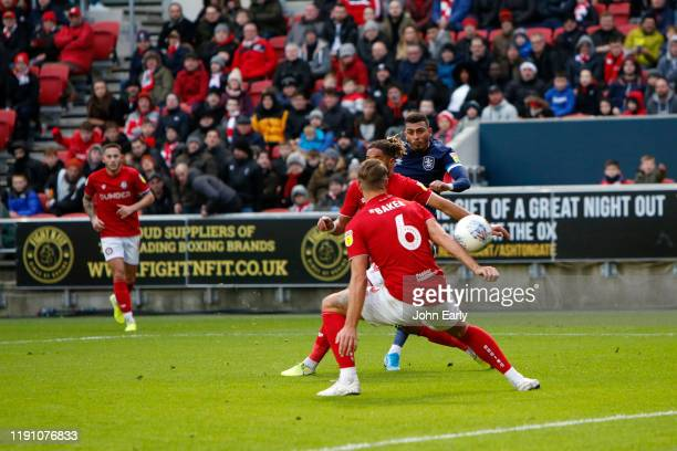 Karlan Grant of Huddersfield Town cuts between Ashley Williams and Nathan Baker of Bristol City to score during the Sky Bet Championship match...