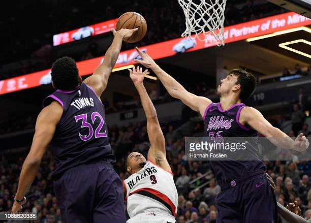 KarlAnthony Towns and Dario Saric of the Minnesota Timberwolves block a shot by CJ McCollum of the Portland Trail Blazers during the fourth quarter...