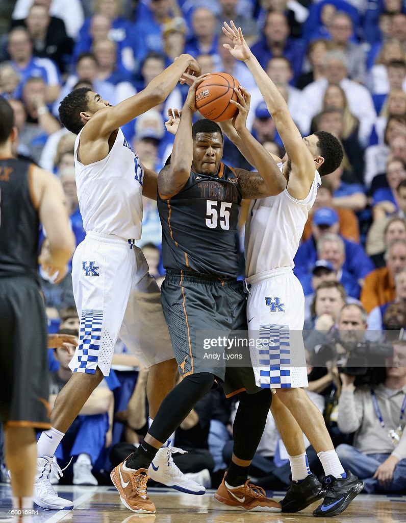 Karl-Anthony Towns #12 and Devin Booker#1 of the Kentucky Wildcats defend Cameron Ridley #55 of the Texas Longhorns at Rupp Arena on December 5, 2014 in Lexington, Kentucky.