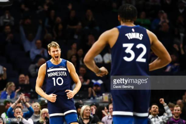 KarlAnthony Towns of the Minnesota Timberwolves celebrates with Jake Layman after Layman scored a basket in the third quarter during the game against...