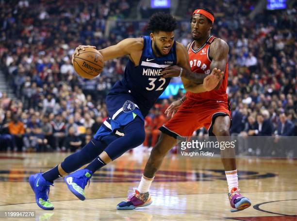 Karl-Anthony Towns of the Minnesota Timberwolves dribbles the ball as Rondae Hollis-Jefferson of the Toronto Raptors defends during the first half of...