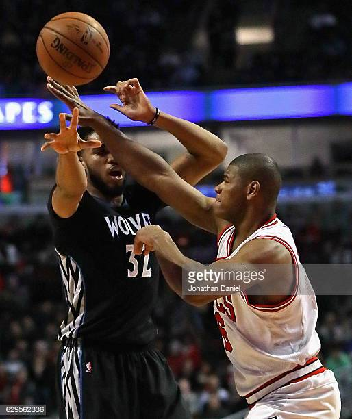 Karl-Anthony Towns of the Minnesota Timberwolves gets off a pass under pressure from Cristiano Felicio of the Chicago Bulls at the United Center on...