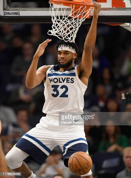 KarlAnthony Towns of the Minnesota Timberwolves hangs on the rim after dunking the ball against the Miami Heat during the first quarter of the home...