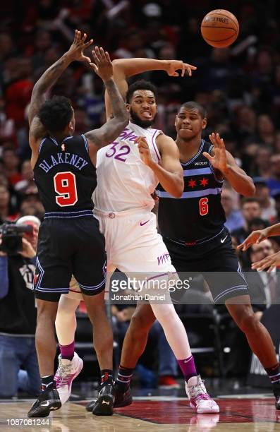 KarlAnthony Towns of the Minnesota Timberwolves passes over his head under pressure from Antonio Blakeney and Cristiano Felicio of the Chicago Bulls...