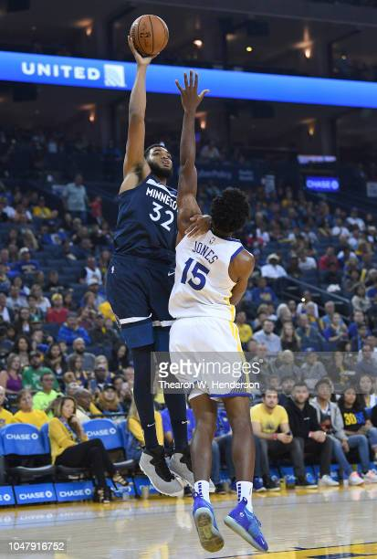 KarlAnthony Towns of the Minnesota Timberwolves shoots over Damian Jones of the Golden State Warriors during an NBA basketball game at ORACLE Arena...