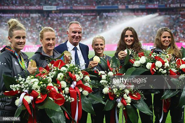 KarlHeinz Rummenigge CEO of Bayern Muenchen pose with team members of Women's football Olympic Gold Medal team prior to the Bundesliga match between...