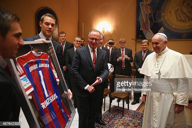 KarlHeinz Rummenigge CEO of FC Bayern Muenchen presents a gift with his players Manuel Neuer and Philipp Lahm for Pope Francis during an private...