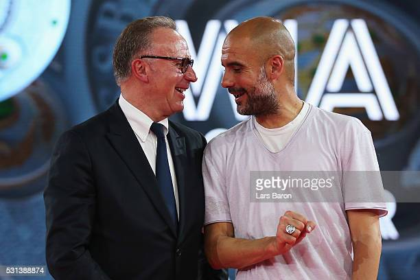 KarlHeinz Rummenigge CEO of FC Bayern Muenchen speaks to Head Coach Pep Guardiola on stage after they receive their Championshop rings during the FC...