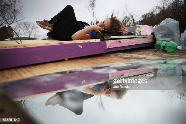 Karlian Mercado rests on the rubble that remains of her families home after it was blown away by Hurricane Maria as it passed through the area on...