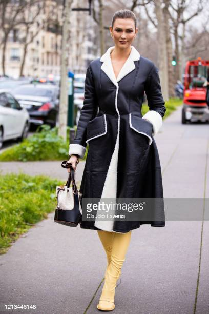 Karlie Kloss, wearing a black leather coat, Loewe bag and yellow boots, is seen outside Loewe, during Paris Fashion Week - Womenswear Fall/Winter...