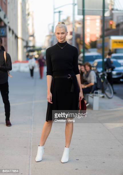 Karlie Kloss wearing black longshirt, black skirt, white heels, red bag seen in the streets of Manhattan outside Diane von Furstenberg during New...