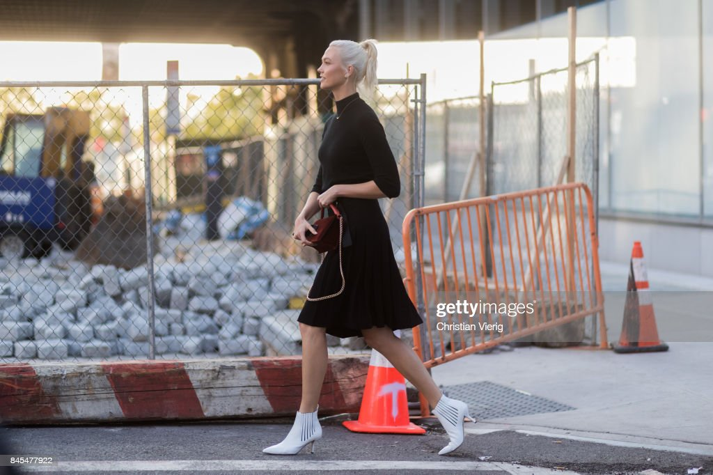 Karlie Kloss wearing black longshirt, black skirt, white heels, red bag seen in the streets of Manhattan outside Diane von Furstenberg during New York Fashion Week on September 10, 2017 in New York City.