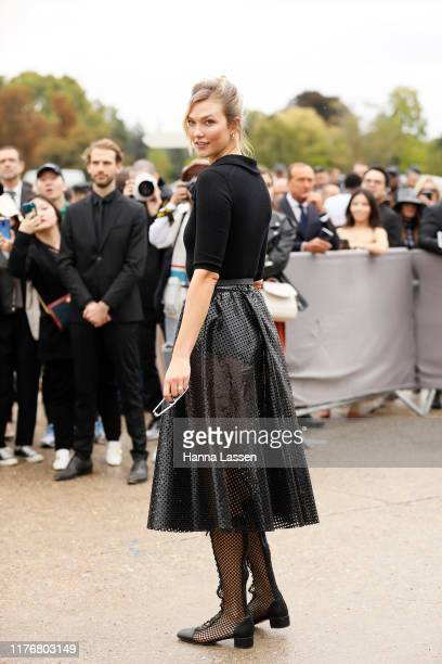 Karlie Kloss wearing black top and see through dotted skirt outside Dior on September 24, 2019 in Paris, France.