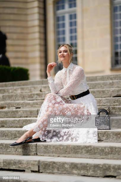 Karlie Kloss wears a white lace dress, outside Dior, during Paris Fashion Week Haute Couture Fall Winter 2018/2019, on July 2, 2018 in Paris, France.