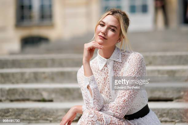 Karlie Kloss wears a white lace dress outside Dior during Paris Fashion Week Haute Couture Fall Winter 2018/2019 on July 2 2018 in Paris France