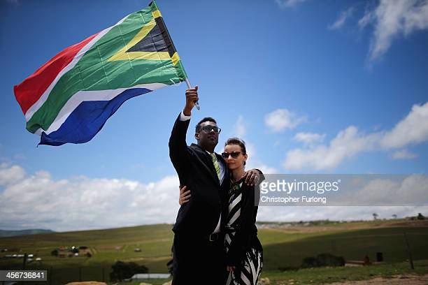 Karlind Govender and his wife Katharina of Cape Town overlook the burial site as a 21 gun salute is fired in honour of former South African President...