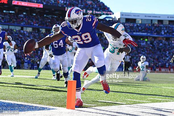 Karlos Williams of the Buffalo Bills scores a touchdown past Michael Thomas of the Miami Dolphins during the first half at Ralph Wilson Stadium on...