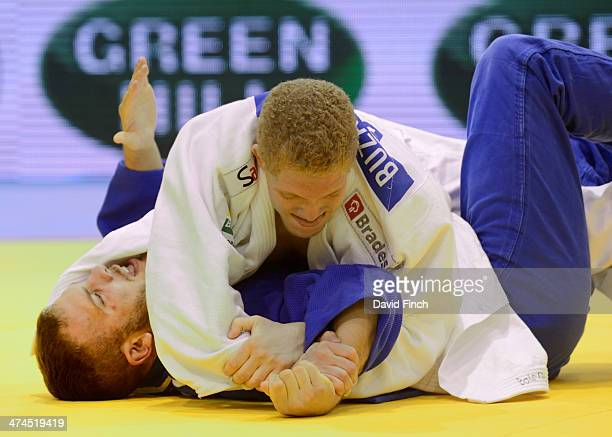 KarlRichard Frey of Germany taps wildly to submit as Rafael Buzacarini of Brazil applies a figure four armlock to win the u100kg bronze medal during...