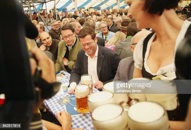 KarlTheodor zu Guttenberg of the Christlich Soziale Union cheers with beer mugs in a fest tent beside of CSU general secretary Andreas Scheuer at the...