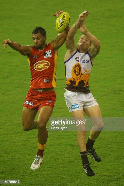 Karmichael Hunt of the Suns and Ryan Harwood of the Lions compete for a mark during the round one NAB Cup AFL match between the Gold Coast Suns and...
