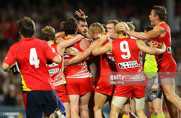 Karmichael Hunt of the Suns celebrates with team mates after kicking the match winning goal after the final siren during the round 16 AFL match...