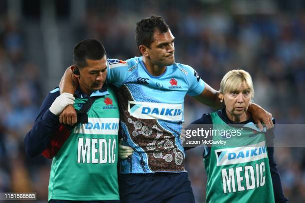Karmichael Hunt of the Waratahs is assisted from the field injured during the round 15 Super Rugby match between the Waratahs and the Jaguares at...