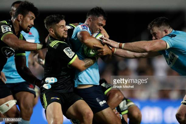 Karmichael Hunt of the Waratahs is tackled during the round one Super Rugby match between the Waratahs and the Hurricanes at Brookvale Oval on...
