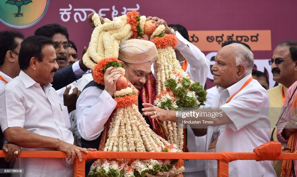 Karnataka BJP state President BS Yeddyurappa and Union Minister Sadanand Gowda welcome BJP national President Amit Shah with garland during a public rally near Devanahalli, on August 12, 2017 in Bengaluru, India. Shah is on a three-day visit to Karnataka starting Saturday as part of his 110-day nationwide tour to strengthen the party. Shah said that he had come here to realise the resolution of forming the next BJP government in Karnataka.