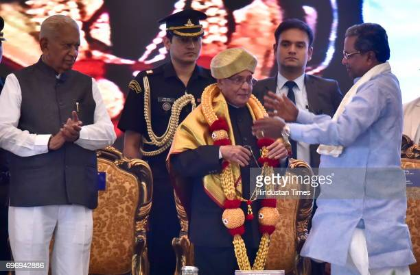 Karnataka Chief Minister Siddaramaiah felicitates President Pranab Mukherjee as Karnataka Governor Vajubhai Rudabhai Vala looks on during the...