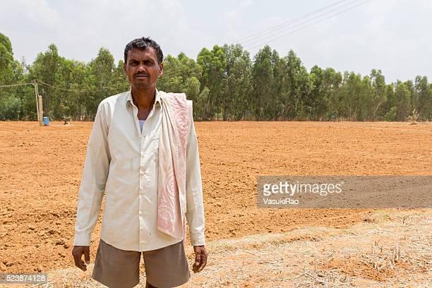 Karnataka farmer stands on barren field, India