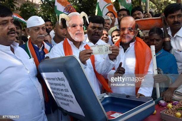 Karnataka Pradesh Congress Committee member sports a caricatured mask of the prime minister of India Narendra Modi and Finance Minister Arun Jaitley...