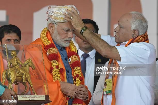 Karnataka state BJP leader BS Yeddyurappa puts a traditional turban on Indian Prime Minister Narendra Modi during a gathering 'Parivarthana Rally' in...