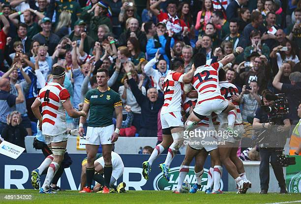 Karne Hesketh of Japan celebrates with his teammates following his winning try during the 2015 Rugby World Cup Pool B match between South Africa and...