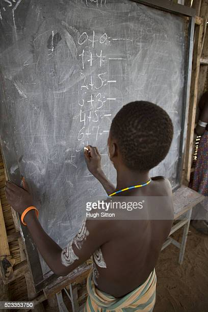 karo boy writing on blackboard during class - hugh sitton ethiopia stock pictures, royalty-free photos & images