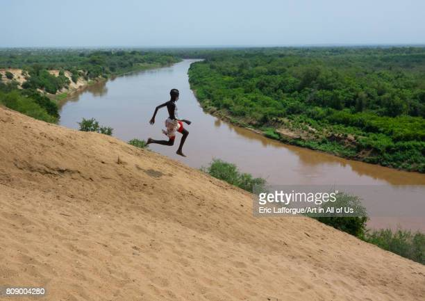 Karo tribe boy jumping in front of Omo river bank Omo valley Korcho Ethiopia on June 11 2017 in Korcho Ethiopia