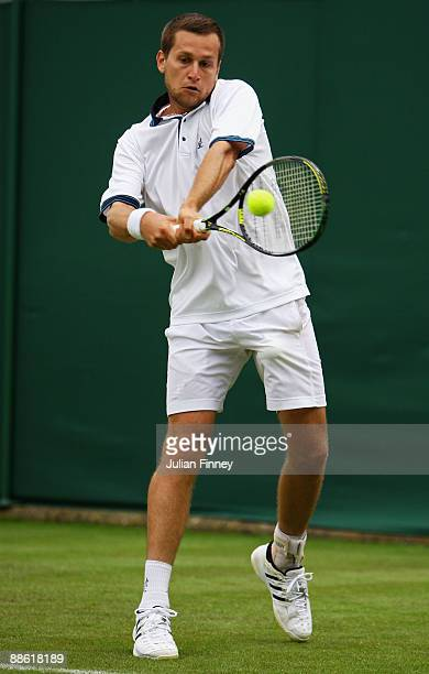 Karol Beck of Slovakia plays a backhand during the men's singles first round match against Feliciano Lopez of Spain on Day One of the Wimbledon Lawn...