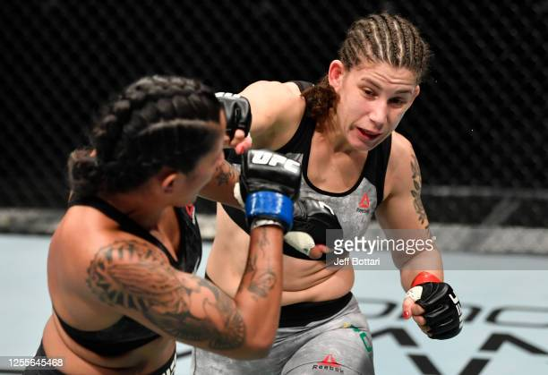 Karol Rosa of Brazil punches Vanessa Melo of Brazil in their bantamweight fight during the UFC 251 event at Flash Forum on UFC Fight Island on July...
