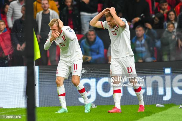 Karol Swiderki and Tymoteusz Puchacz of Poland being thrown with objects by Albania fans after a goal has been scored during the 2022 FIFA World Cup...