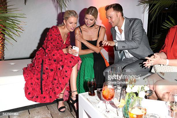 Karolina Kurkova and Lena Gercke and manager Timothy Baines look mobile phone during the Raffaello Summer Day 2016 to celebrate the 26th anniversary...