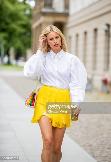 Karolina Kurkova is seen wearing yellow mini skirt with fringes white button shirt bag on July 05 2019 in Berlin Germany