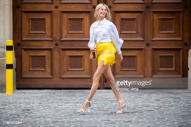 Karolina Kurkova is seen wearing yellow mini skirt with fringes white button shirt bag white heels during Berlin Fashion Week on July 05 2019 in...