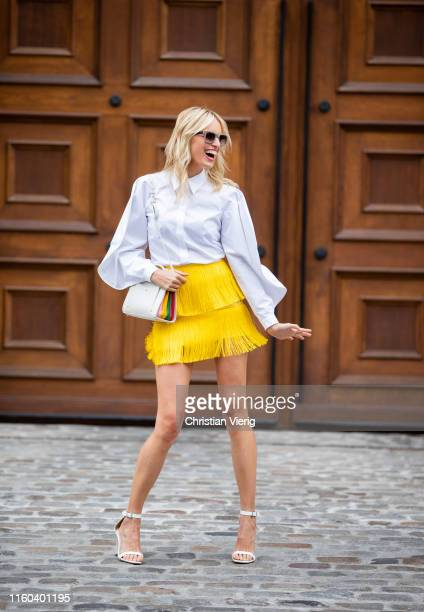 Karolina Kurkova is seen wearing yellow mini skirt with fringes white button shirt bag white heels during Berlin Fashion Week on July 05 2019 in...