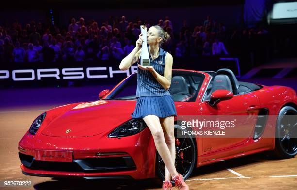 Karolina Pliskova from the Czech Republic kisses her trophy as she poses with her new Porsche Boxster car she got after winning the WTA Tennis Grand...