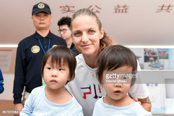 Karolina Pliskova of Czech Repubic poses for a picture with kids at the Harvest fund booth on day five of the 2017 China Open at the China National...
