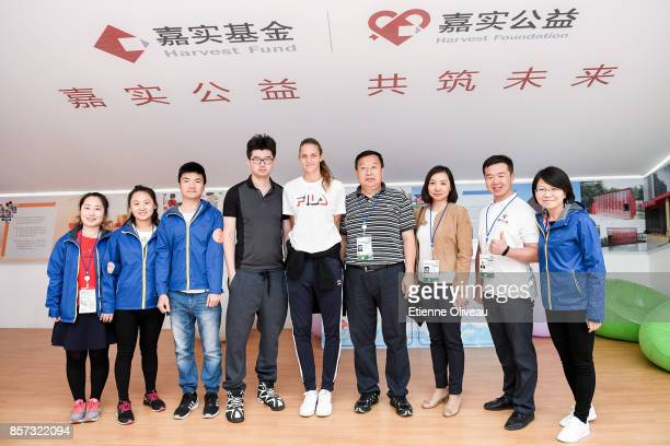 Karolina Pliskova of Czech Repubic poses for a picture with staff members at the Harvest fund booth on day five of the 2017 China Open at the China...