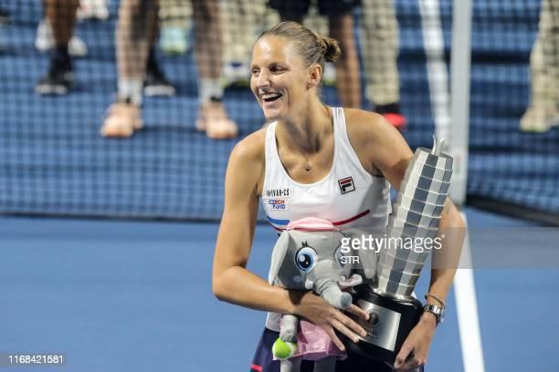 Karolina Pliskova of Czech Republic holds the trophy after winning the women's singles final match against Petra Martic of Croatia at the Zhengzhou...