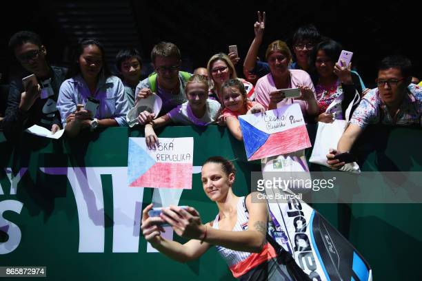 Karolina Pliskova of Czech Republic takes a selfie with fans as she celebrates victory in her singles match against Garbine Muguruza of Spain during...