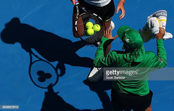 Karolina Pliskova of the Czech Republic and a ball kid exchange balls and towel in her first round match against Kimberly Birrell of Australia during...